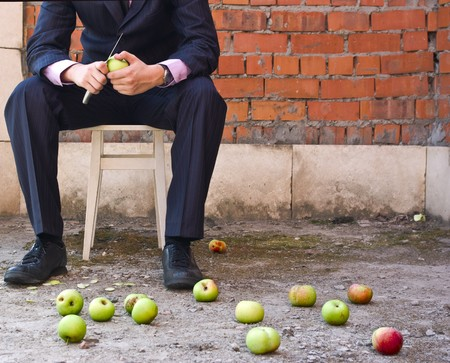the businessman cleaning apples sitting on a stool