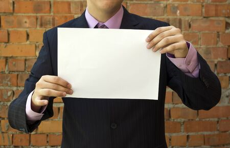 Business young man holding a blank white sheet of paper. Stock Photo - 7627812