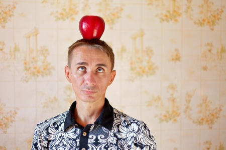 Funny man having apple on his head and looking at it photo