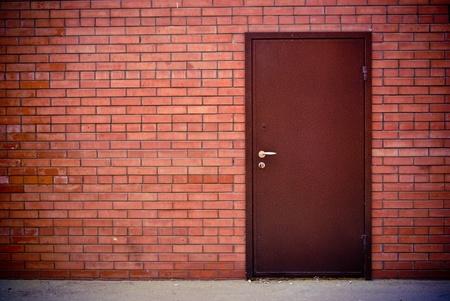 puertas de madera: la pared de ladrillo rojo y el hierro de la puerta cerrada
