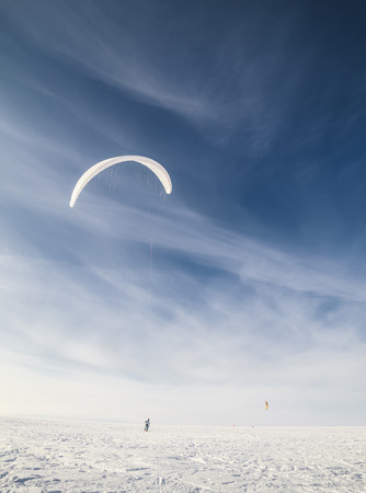 Kite boarder in snowy countryside field with cloudscape background, winter scene photo