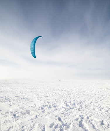 kite surfing: Kite surfer being pulled by his kite across the snow