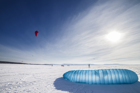 Kite surfer being pulled by his kite across the snow photo