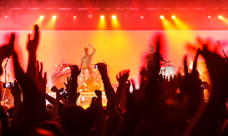 cheer: Silhouettes of concert crowd in front of bright stage lights Illustration