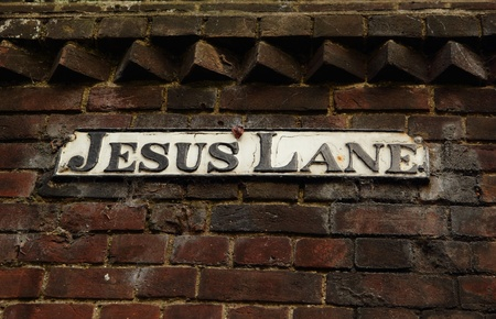 A road sign with Jesus Lane on a brick wall