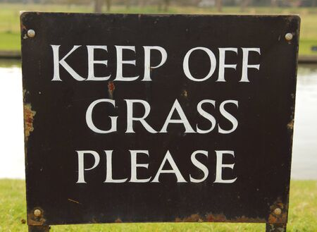 A keep of the grass sign in a park