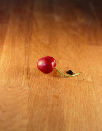 A cherry on a wooden table Stock Photo