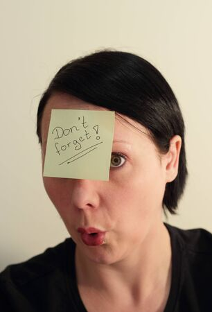 A woman with a Don�t forget note on her forhead