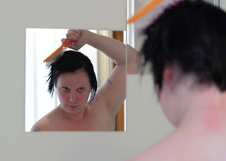 A woman is brushing her wet hair photo