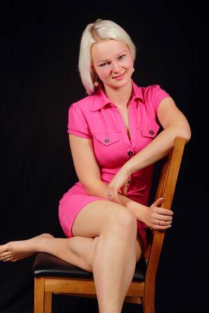 belles jambes: Une femme dans une robe rose est assis sur une chaise Banque d'images