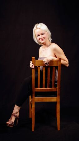 Blonde woman is posing with a chair Stock Photo