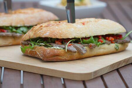 steak sandwich: Steak sandwich on a wooden board