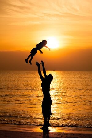 Silhouette of father carrying his child on the beach during sunset.