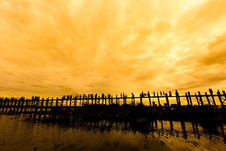 pedestrian bridges: Silhouetted people on U Bein bridge at sunset Mandalay, Myanmar