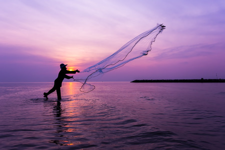 Silhouette of fisherman throwing net at sunset.