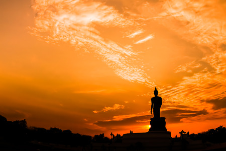 Silhouette big buddha statue in sunset background.
