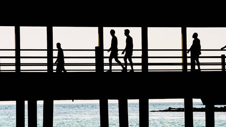 persone nere: Silhouette of people walking across the bridge.