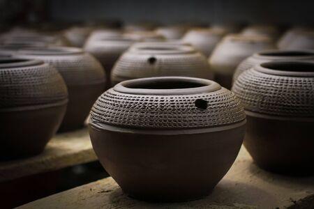 ollas de barro: macetas de arcilla con motivos hermosos tallados en una fila Foto de archivo
