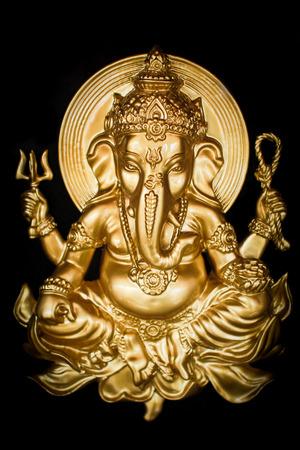 Golden hindu god ganesh on a black background. Stock Photo