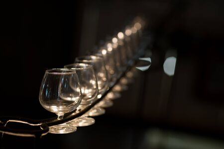 bar ware: Brandy glasses hang up side down. Brandy glass empty. Stock Photo