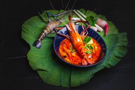 Thai food - Tom yum kung, River prawn spicy soup on on the lotus leaf background.