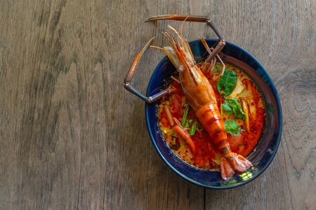 Thai food - Tom yum kung, River prawn spicy soup on on the  wood background.