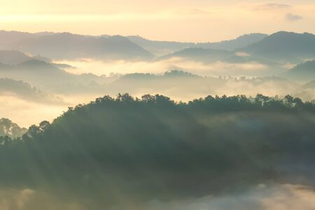 Beautiful Landscape of mountain layer in morning sun ray and winter fog. Stock Photo