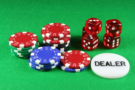 Poker chips and 5 dice on a green baize