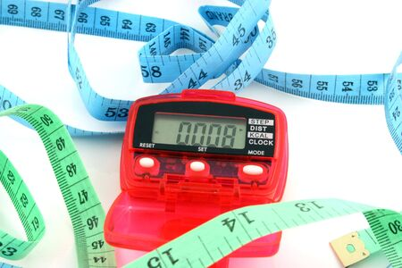 Close up of a Pedometer and 2 tape measures - isolated on a white background   Banco de Imagens