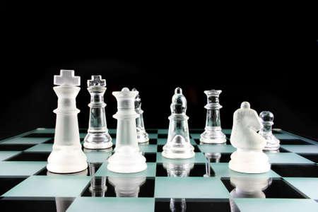 ajedrez: Juego de ajedrez - Las piezas de ajedrez sobre un tablero de ajedrez de vidrio