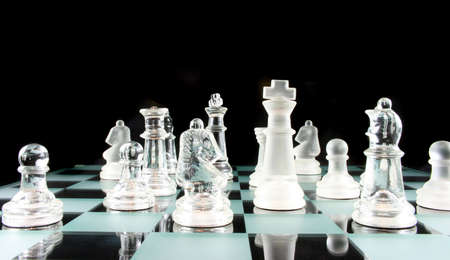 Glass Chess Pieces on a Frosted Glass Chess Board   photo