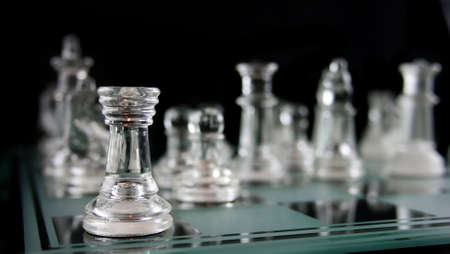 outwit: Glass Chess Pieces on a Frosted Glass Chess Board   Stock Photo