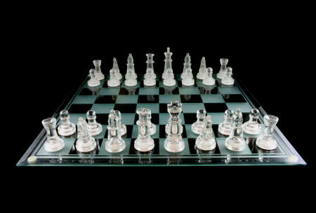 strategize: Glass Chess Pieces on a Frosted Glass Chess Board fully isolated on black
