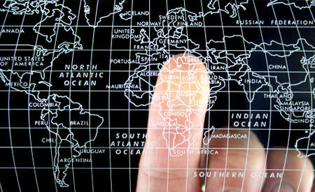 Finger pointing at a World map