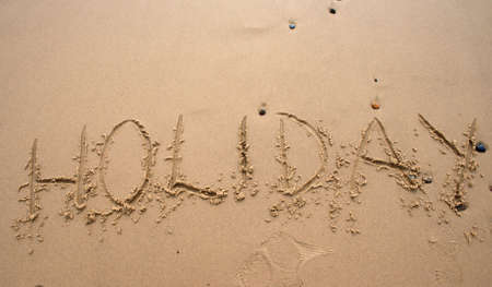 The word Holiday written in sand next to the shore
