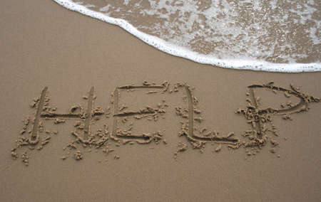 The word Help written in sand next to the shore with a wave washing over