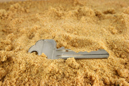 bury:  A key lost on the beach and half buried in the sand