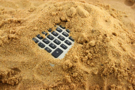A Calculator half buried in the sand  Banco de Imagens