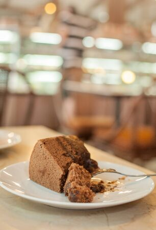a slice of chocolate cake on white plate with bokeh backgroung