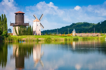 windmill reflection on the water with blue sky background Stock Photo