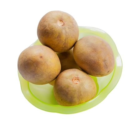 fresh sapodilla in a green bowl isolated on white background Stock Photo