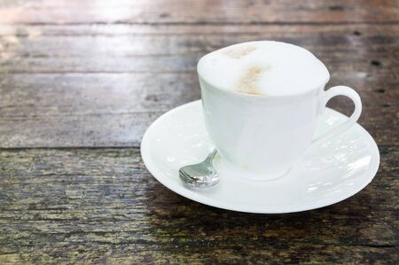 Coffee with milk froth in a white cup on wooden background