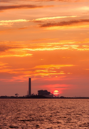 Silhouette of electrical power plant against sunset photo