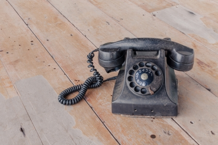 Retro black old telephone on wooden background, retro style