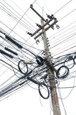 chaotic tangle of wires on electric post isolate on white