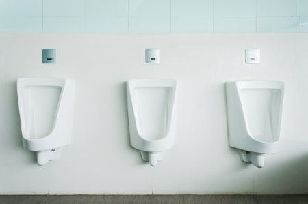 group of white porcelain urinals in public toilets