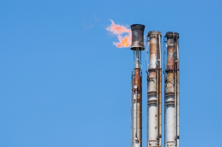 Burning oil flare on a blue sky Stock Photo