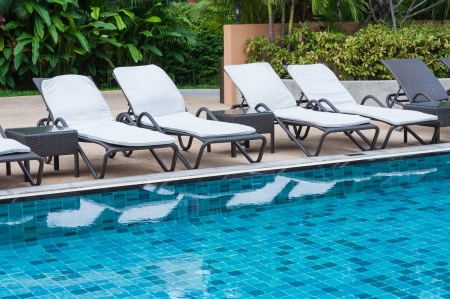 Swimming pool with beach chairs Stock Photo