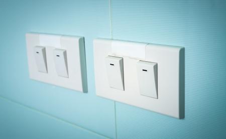 light switch: Electrical white rocker light switch on green wall