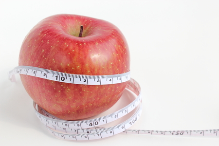 An apple and tape measure Stock Photo